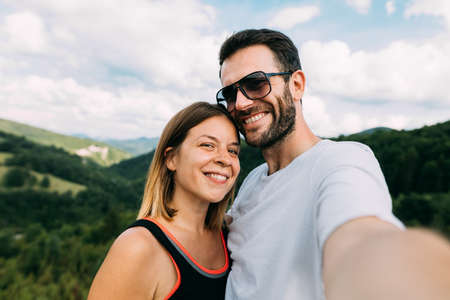 Young couple taking a selfie in the mountains