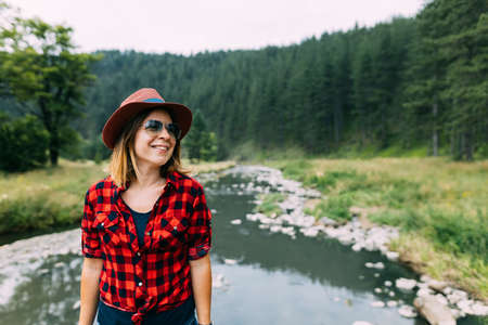 Young woman enjoying the great outdoors by the river in the mountains Standard-Bild