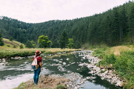 Young woman enjoying the great outdoors by the river in the mountains