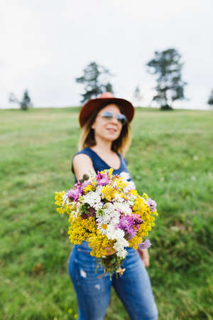 Young woman holding flower bouquet  in the field Standard-Bild