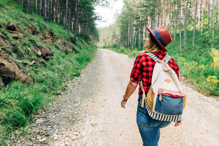 Young female nature explorer walking on mountain dirt road