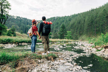 Young couple exploring nature by the mountain river Standard-Bild