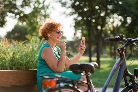 Mature woman using video call on her smartphone in the park