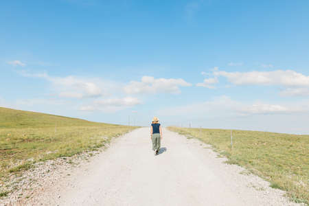 Young female nature explorer walking on a gravel road in summertime Standard-Bild