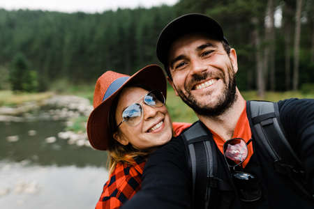 Selfie of a young couple in the mountains by the river