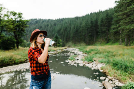 Young female nature lover drinking water from the bottle by the river