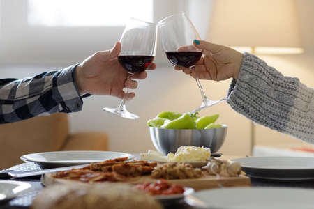 Two glasses of wine cheering over the dinning table 版權商用圖片