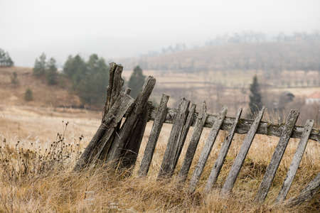 Rustic fence in the countryside on foggy morning