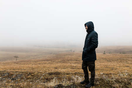 Young man exploring nature on a wet winter morning in the mountains
