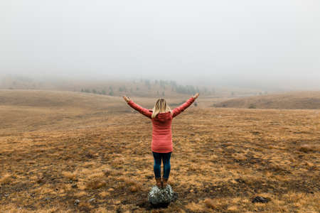 Young woman exploring nature in the foggy winter morning