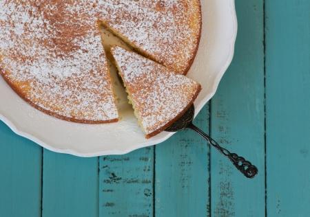 rebanada de pastel: Tarta de lim�n en un plato blanco y mesa de color turquesa