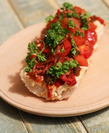 Baguette with roasted vegetables, hummus and parsley on wooden plate photo
