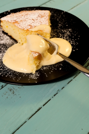 afternoon fancy cake: Lemon cake with lemon cream on black plate with fork Stock Photo