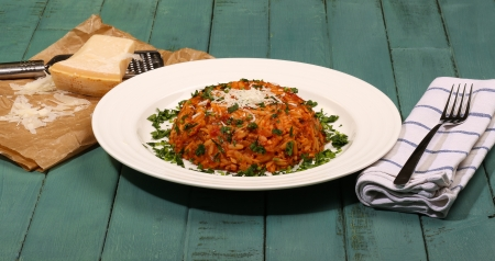 Yiouvetsi - One Pot Greek Ground Lamb with Kritharaki  Orzo , Tomato, Cinvamon, Cloves, Parsley and Parmesan Cheese on Rustic Turquoise table Stock Photo