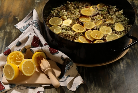 cordial: Third step in making the Elderflower cordial - prepare lemon juice from fresh lemons, boil the watter with cane shugar and pour over Elderflowers in the bowl  Leave to rest covered for three days and then strain into sterilized bottles