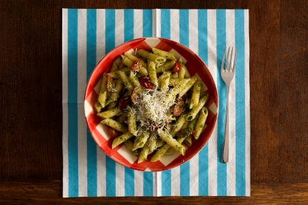 Pasta with pesto sauce with parsley, parmesan cheese and tomato on gingham plate turquoise napkin and fork on rustic oak table Stock Photo