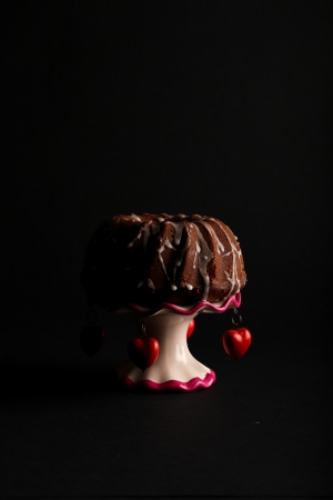 Chocolate pound  bundt  cake with icing on antic stand with red hearts on dark background Stock Photo - 20889873