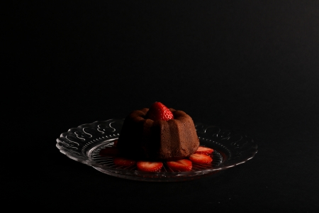 Chocolate mini pound  bundt  cake with strawberry on top and sliced strawberries on glass plate and dark background Stock Photo - 20889881