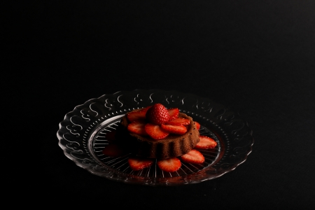 Chocolate mini sponge cake with strawberry on top and sliced strawberries on glass plate and dark background Stock Photo - 20889886