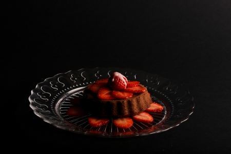 Lemon vanilla mini sponge cake with strawberry on top and sliced strawberries on glass plate and dark background photo