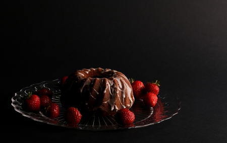 Chocolate pound  bundt  cake icing and strawberries on glass plate and dark background photo