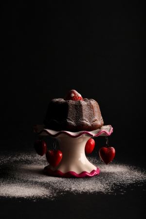 Chocolate mini pound  bundt  cake with strawberry on top and icing sugar on antic stand with red hearts and icing sugar on dark background photo