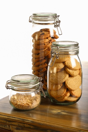 Chocolate and lavender cookies and crushed hazelnuts in a jar on rustic table and white background photo