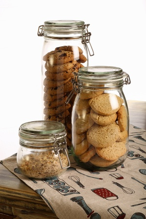 Chocolate and lavender cookies and crushed hazelnuts in a jar on rustic table with tablecloth and white background photo
