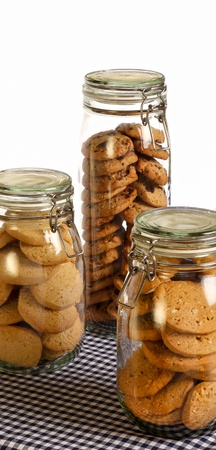 Chocolate, lavender and hazelnut cookies in a jar on rustic table with dark blue gingham tablecloth and white background photo