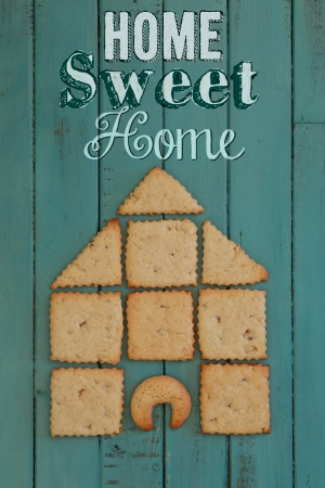 Ginger Cookies Stacked as house on turquoise wooden board, copy space