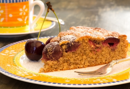 Cherry almond cake with fresh cherries, fork,  bright yellow plate and orange cup
