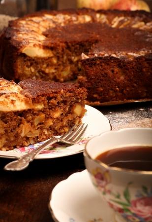Apple Cinnamon cake on backing paper, slate plate with hazelnuts, cinnamon sticks, apples, lemon and Coffee cup photo