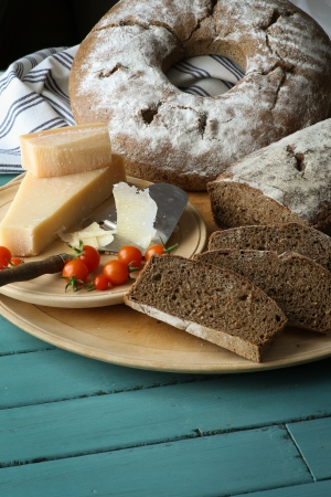 Traditional country style wheat rye wholemeal bread with parmesan cheese and cherry tomatoes on cutting board and rustic turquoise table