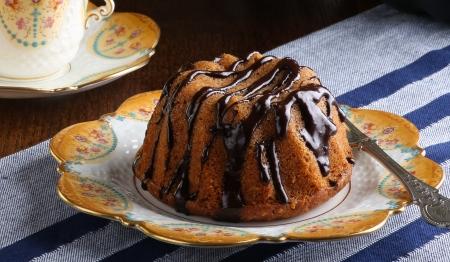 Mini Pound Cake - Haselnuss-Kuchen mit Schokolade bedeckt mit alten Bildern Kaffeetasse und Teller
