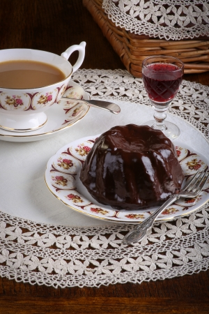 Mini Pound Cake - Chocolate hazelnut cake on old pictures tea cup, side plate on lace and red wine liquor