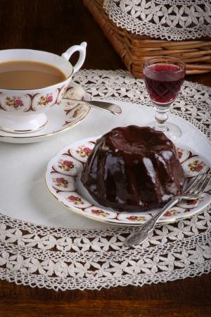 Mini Pound Cake - Schokoladen-Haselnuss-Kuchen auf alten Bildern Tasse Tee, Teller auf Spitze und Rotwein Schnaps