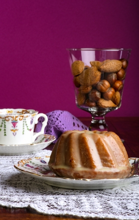 Mini Pound Cake - Almond lemon drizzle cake on old pictures coffee cup, side plate on lace and glass cup full of almonds and hazelnuts, purple background
