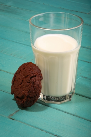 Dark chocolate cookies with milk in glass on turquoise rustic table Stock Photo