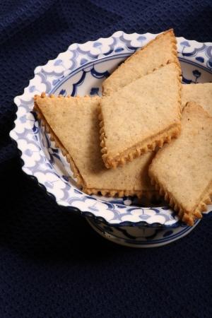 Hazelnut biscuits on antique blue stand and dark blue background