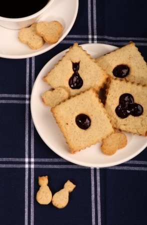 Hazelnut biscuits - cat shaped cookies with mixed berry jam on white plate, coffee mug, dark blue striped tablecloth Stock Photo
