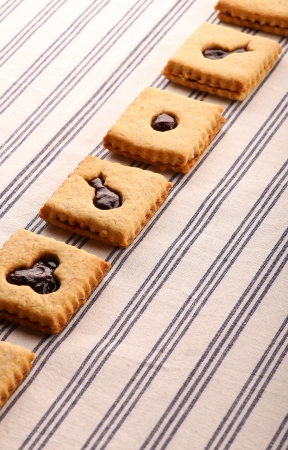 Hazelnut biscuits cookies with mixed berry jam  on striped tablecloth