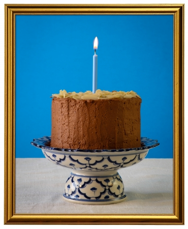 Chocolate birthday party cake with almond flakes and burning candle on antique ceramic stand with blue pattern, blue background, white canvas, isolated golden frame