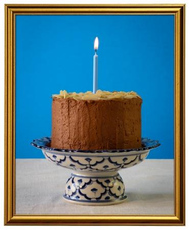 Schokoladen-Geburtstags-Party Kuchen mit Mandelbl�ttchen und brennende Kerze auf antiken Keramik Stand mit blauem Muster, blauem Hintergrund, wei�en Leinwand, isoliert goldenen Rahmen