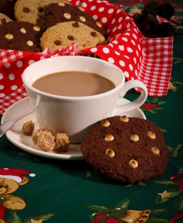 White and dark chocolate chip cookies with glass of milk green tablecloth christmas pattern
