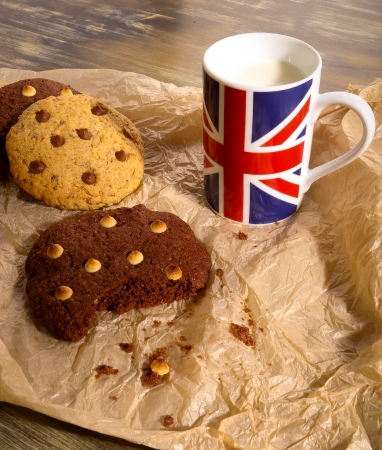 drapeau anglais: Blanc et noir biscuits aux brisures de chocolat avec du lait dans la tasse de drapeau anglais sur papier froiss� brun clair