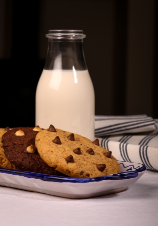 White and dark chocolate chip cookies on ceramic tray with small bottle of milk Stock Photo