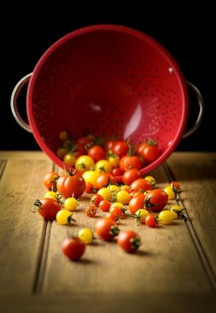 Gelbe Sonne und Cherry-Tomaten, roten Sieb, rustikalen Tisch, dunklen Hintergrund Lizenzfreie Bilder