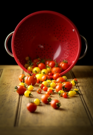 Yellow sun and cherry tomato, red strainer, rustic table, dark background