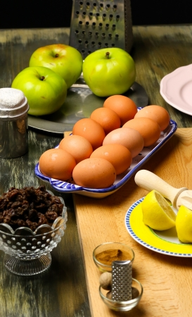 Apple pie ingredients, eggs, green apples, lemon, cinnamon, butter, raisins, icing sugar photo