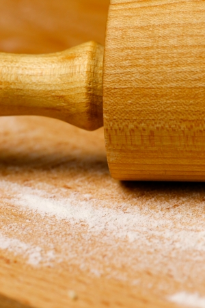 Wooden rolling pin with white wheat flour on the table Stock Photo - 22839728
